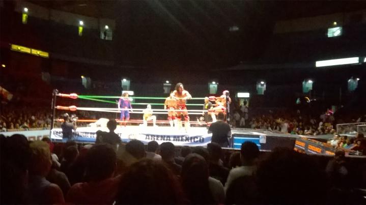 Luchadores en acción en el ring de la arena México